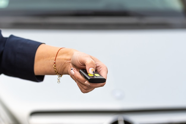 Woman hand holding the car remote, he push the remote control to open the car door