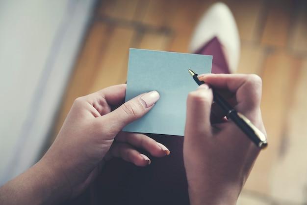 カードとペンを持つ女性の手