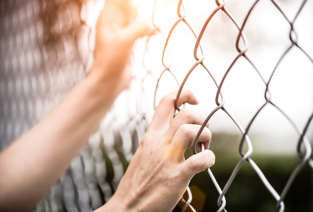 Woman hand holding on chain link fence for remember human rights day