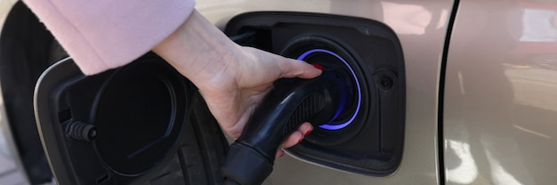 Woman hand holding charger for car closeup