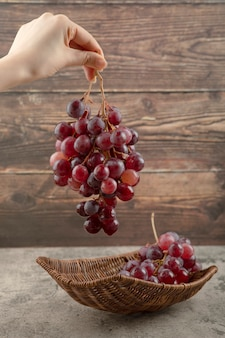 Woman hand holding cluster of red grapes on wooden background.