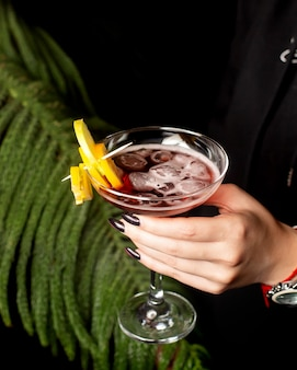 Woman hand holding a cocktail glass with fruit pieces on bamboo skewer