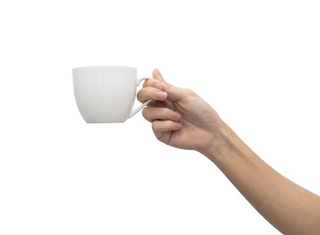 白い背景の上のコーヒーカップ分離株を持っている女性の手