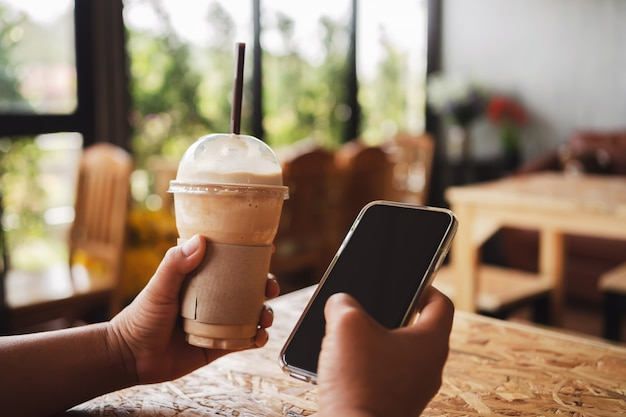 Woman hand holding coffee in plastic cup and mobile phone in shop