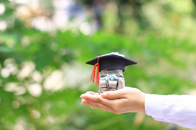 Woman hand holding coins money in glass bottle with graduates hat on natural green background