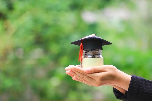 Рука женщины держа деньги монеток в стеклянной бутылке с шляпой выпускников, сохраняя деньги для концепции образования