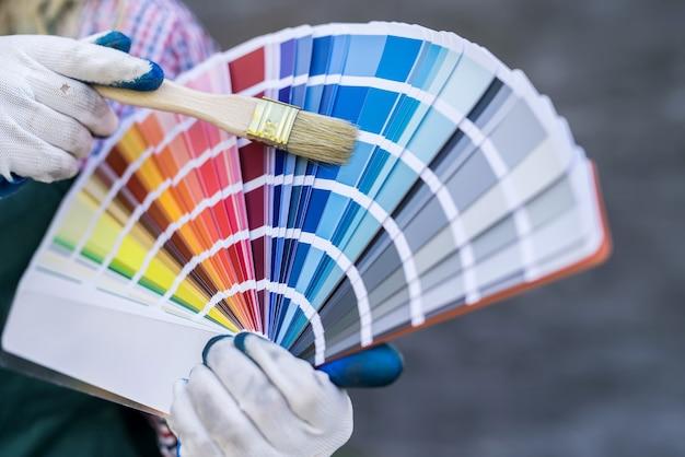 修理のためのカラーパレットを持っている女性の手。リノベーションコンセプト