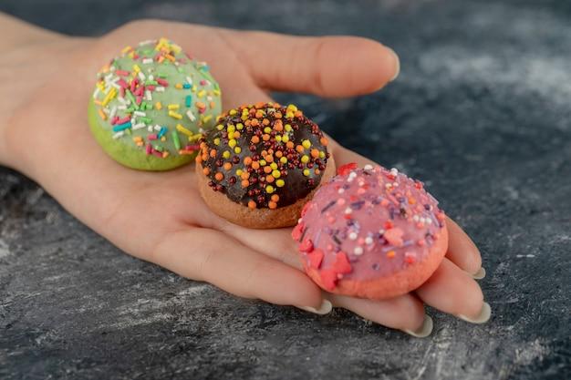 カラフルな甘いドーナツを振りかける女性の手。