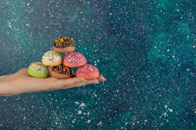 여자 손 뿌리와 화려한 달콤한 도넛을 들고.