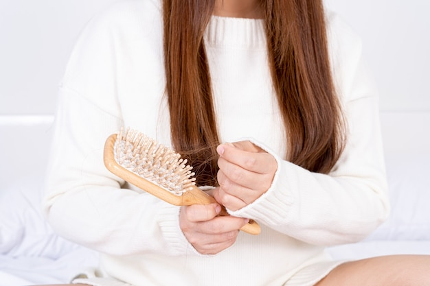 Woman hand holding comb with hair stuck on it on white background