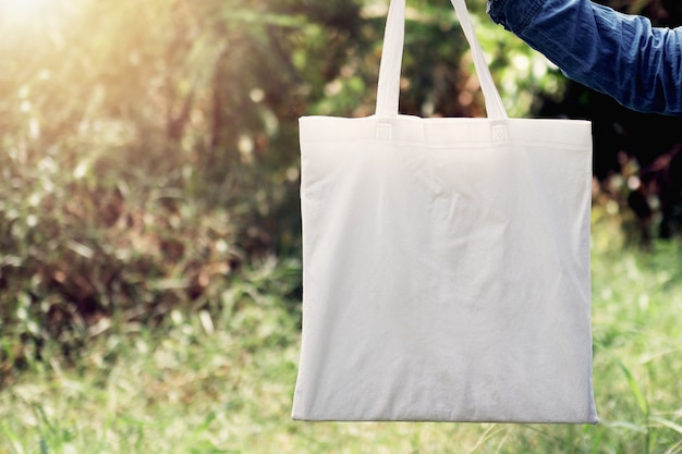 Woman of hand holding cotton tote bag on green grass background. concept eco and recycling