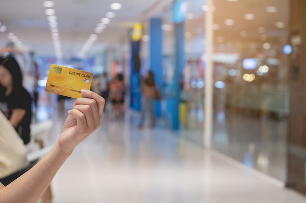 Woman hand holding credit card blurred