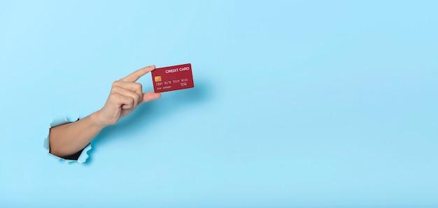 青いバナーの背景にクレジット カードを持っている女性の手。パノラマ画像