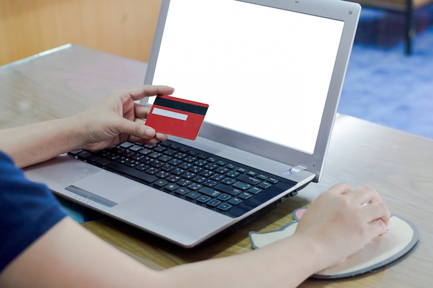 Woman hand holding credit card and using laptop computer.