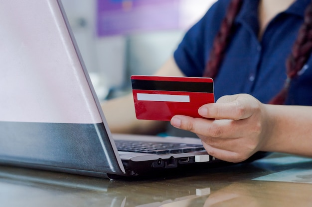 Woman hand holding credit card and using laptop computer