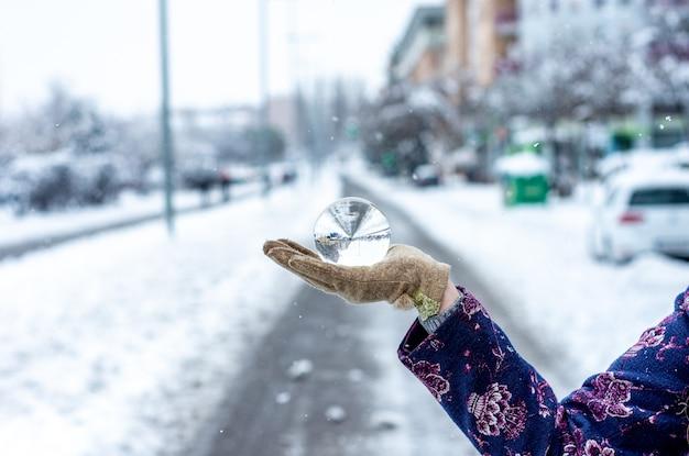 A woman hand holding a crystal ball on a main avenue. snowy urban landscape.