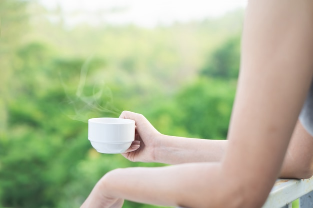 Woman hand holding cup of hot coffee drinking outdoors