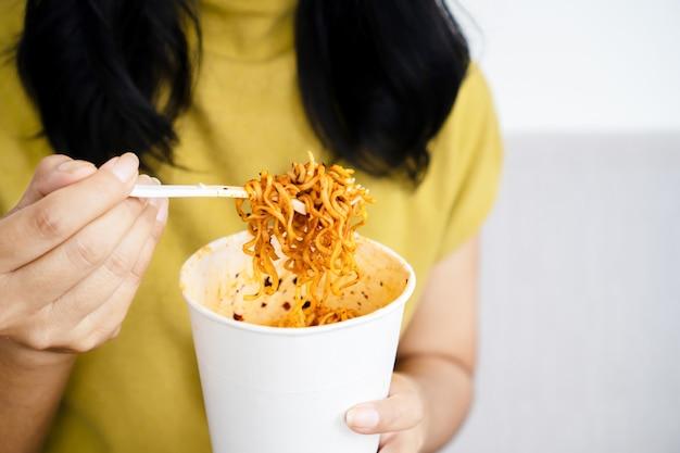 スパイシーな麺のカップを持っている女性の手麺を食べる女性のクローズアップ