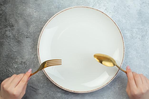Posate della holding della mano della donna impostate sul piatto vuoto sulla superficie grigia