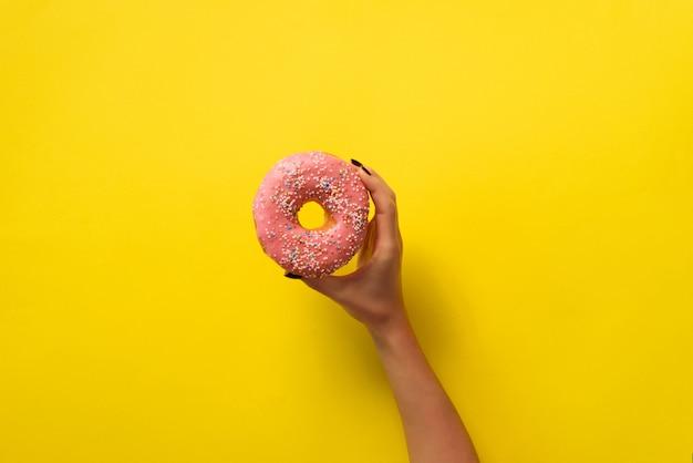 Рука женщины держа очень вкусный розовый донут на желтой предпосылке цвета.