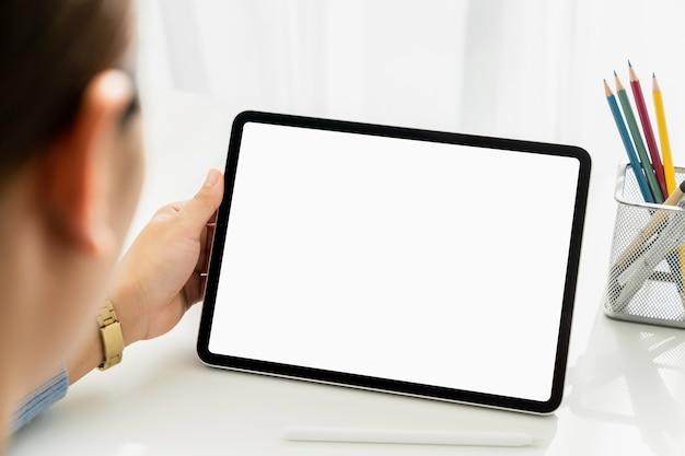 テーブルの上にデジタルタブレットを持っている女性の手と画面が空白です。
