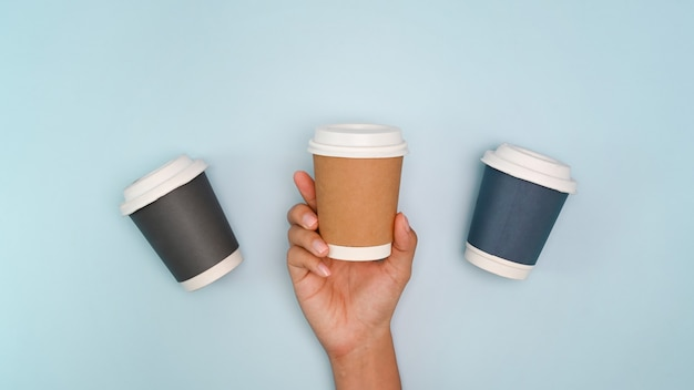 Woman hand holding disposable paper cup on blue pastel background. eco friendly concept.