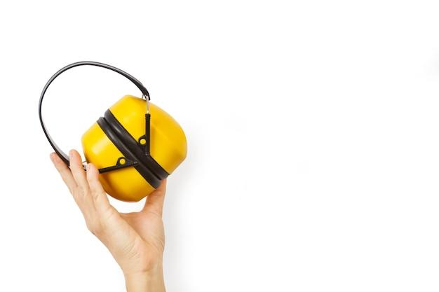 安全保護ヘッドホンを聞くためのイヤーマフを持っている女性の手