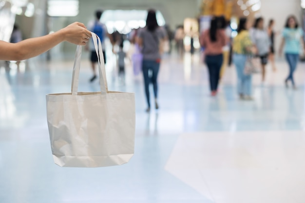 Woman hand holding eco shopping bag in store  with copy space for text. environmental protection, zero waste, reusable, say no plastic, world environment day and earth day concept