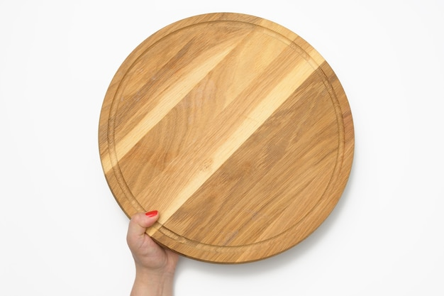 Woman hand holding empty round wooden pizza board in hand, body part on white background