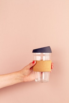 Woman hand holding empty tumbler, reusable coffee mug. plastic free and zero waste lifestyle concept