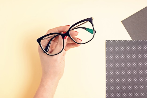 Woman hand holding eyeglasses. optical store, glasses selection, eye test, vision examination at optician, fashion accessories concept. top view, flat lay