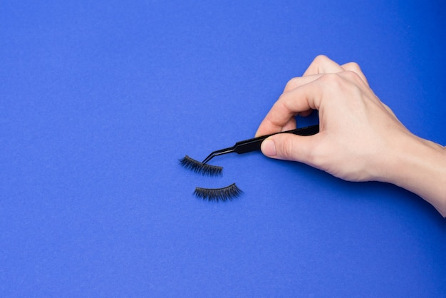 Woman hand holding false eyelashes in pincer on classic blue