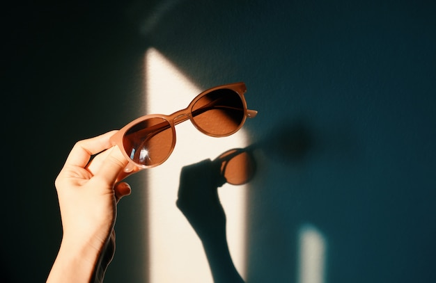 Woman hand holding fashionable sunglasses with shade of sunlight with shadow on wall, trendy and summer concept