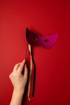 빨간 벽 위에 축제, 화려한 마디 그라 또는 카니발 마스크를 들고 여자 손. 평면 누워, 상위 뷰