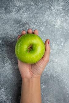 Mano della donna che tiene mela fresca su marmo.