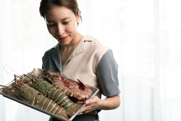 Woman hand holding fresh raw tiger prawn and spiny lobster on white