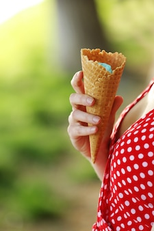 Woman hand holding fresh waffle cone with vanilla and raspberry ice cream