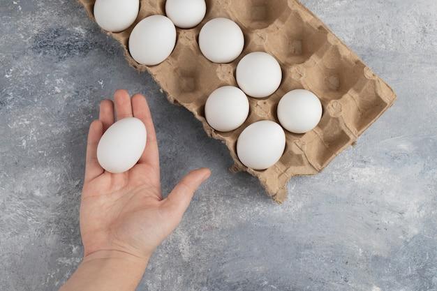 Mano della donna che tiene un uovo di gallina bianco fresco su un marmo.