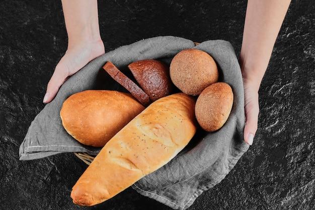 Mano della donna che tiene pane appena fatto in casa.
