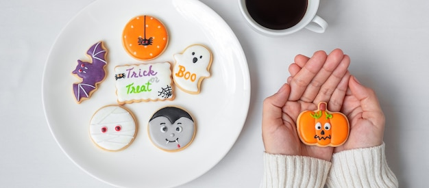 Woman hand holding funny halloween cookie during drinking coffee. happy halloween day, trick or threat, hello october, fall autumn, traditional, party and holiday concept