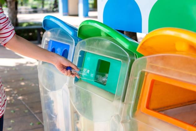 Женщина, держащая пластиковую бутылку для мусора, кладет в пластиковую корзину для мусора