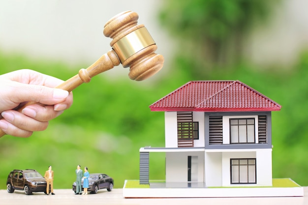 Woman hand holding gavel wooden and model house