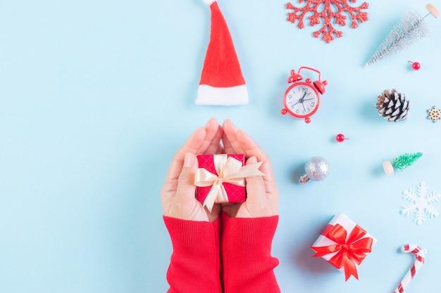パステルブルーのクリスマスの装飾に贈り物を持っている女性の手