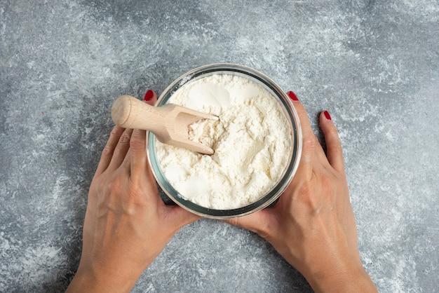 大理石に小麦粉のガラスのボウルを持っている女性の手。