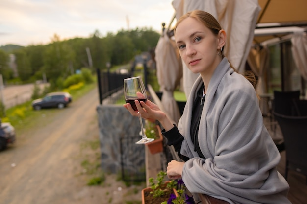 Woman hand holding glass with wine on blurred natural background.
