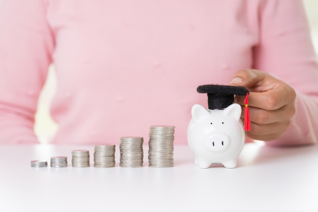 Woman hand holding graduation cap with money coin on stack of coins and piggy bank