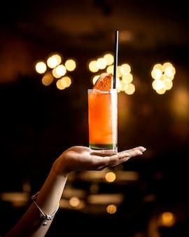 Cocktail di pompelmo della tenuta della mano della donna con paglia nera