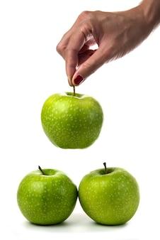 Mano della donna che tiene le mele verdi su bianco.