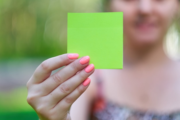 Woman hand holding a green notepaper