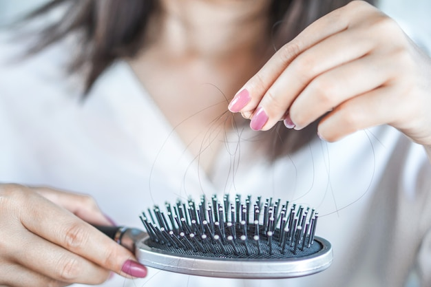 Woman hand holding hair fall on comb
